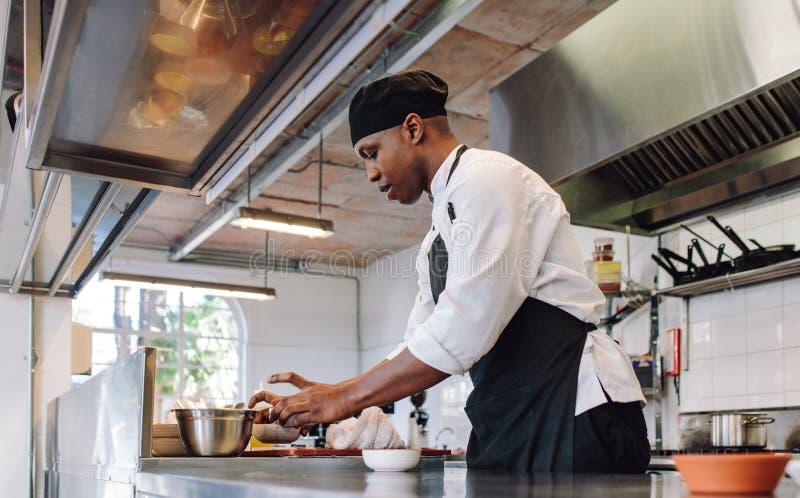 Chef-kok die in een commerciële keuken werken royalty-vrije stock afbeeldingen