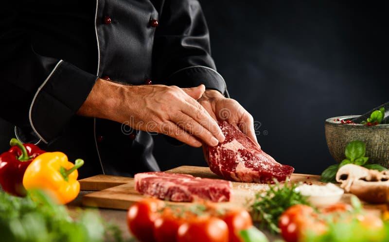 Chef-kok die een dik ruw rundvleeslapje vlees met kruiden kruiden royalty-vrije stock afbeelding