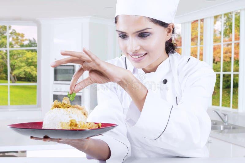 Chef-kok die een schotel in de keuken houden stock afbeelding