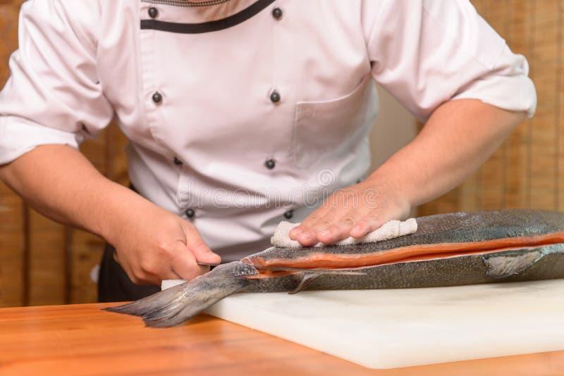 Chef-kok die een verse zalmvis op een scherpe raad voorbereiden stock fotografie