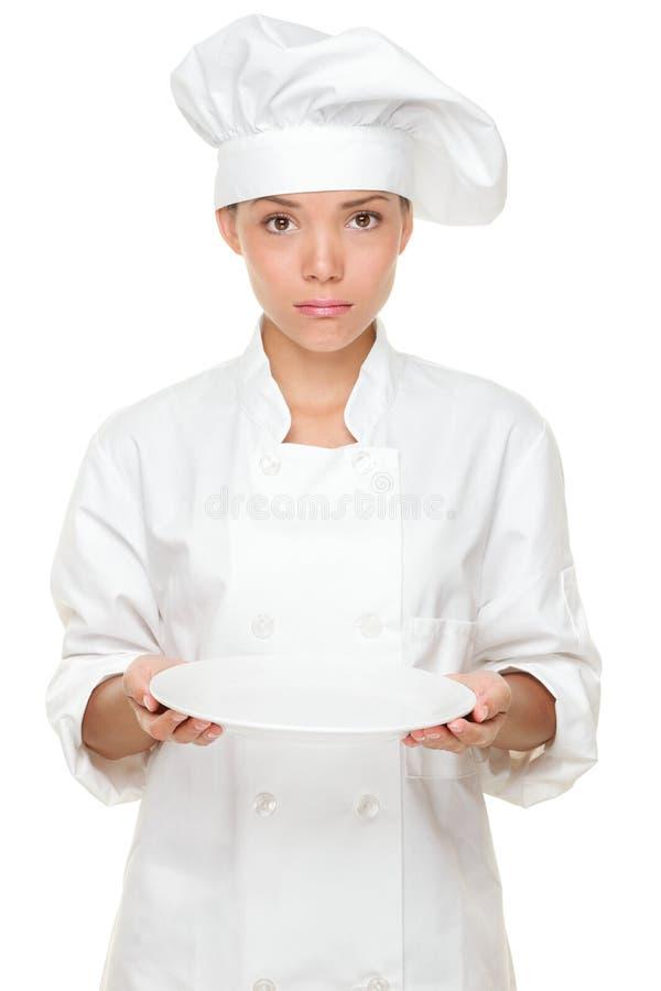 Chef-kok die en droevig met lege plaat wordt teleurgesteld stock foto