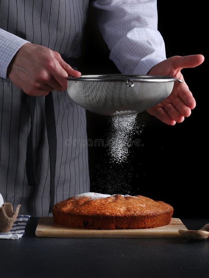 Chef-kok die gepoederde suiker op smakelijke pastei op donkere achtergrond gieten ched verwerkingspastei of cake royalty-vrije stock fotografie