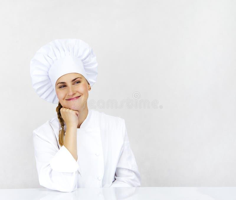 Chef-kok die glimlachend en gelukkig het kijken denkt aan de kant Vrouwenchef-kok, royalty-vrije stock afbeelding