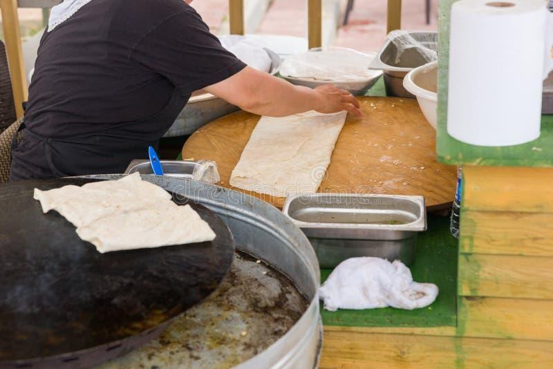 Chef-kok die gozleme flatbread in Anatolië maken stock fotografie