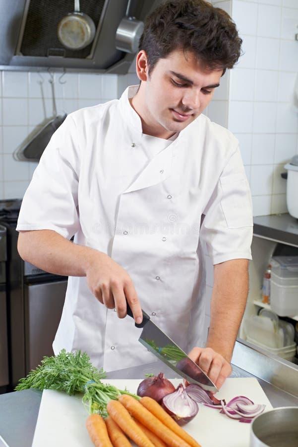 Chef-kok die Groenten in de Keuken van het Restaurant voorbereidt stock afbeeldingen