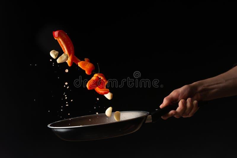 Chef-kok die groenten in een koekepan voorbereiden stock afbeelding