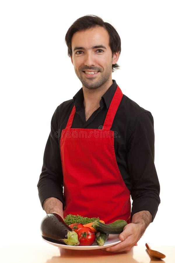 Chef-kok die groenten voorstelt stock afbeelding