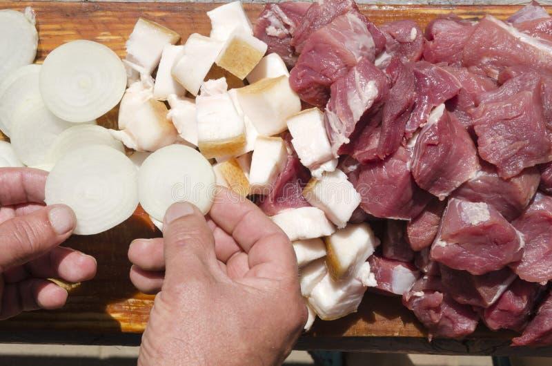 Chef-kok die ingrediënten voor barbecue voorbereiden Ruwe vlees en reuzel, stukken van ui royalty-vrije stock fotografie