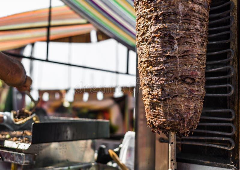 Chef-kok die kebab en grillshawarmavlees voorbereiden bij een markt van het straatvoedsel royalty-vrije stock foto