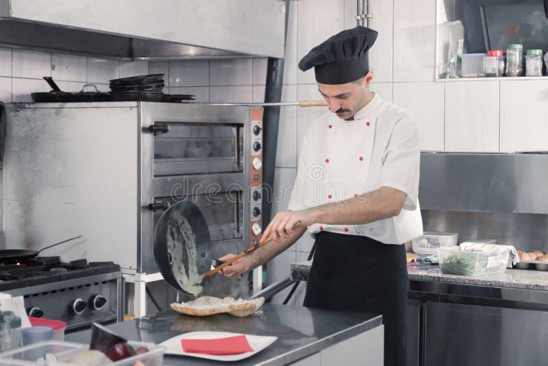 Chef-kok die kokende sandwichpan maken stock afbeeldingen