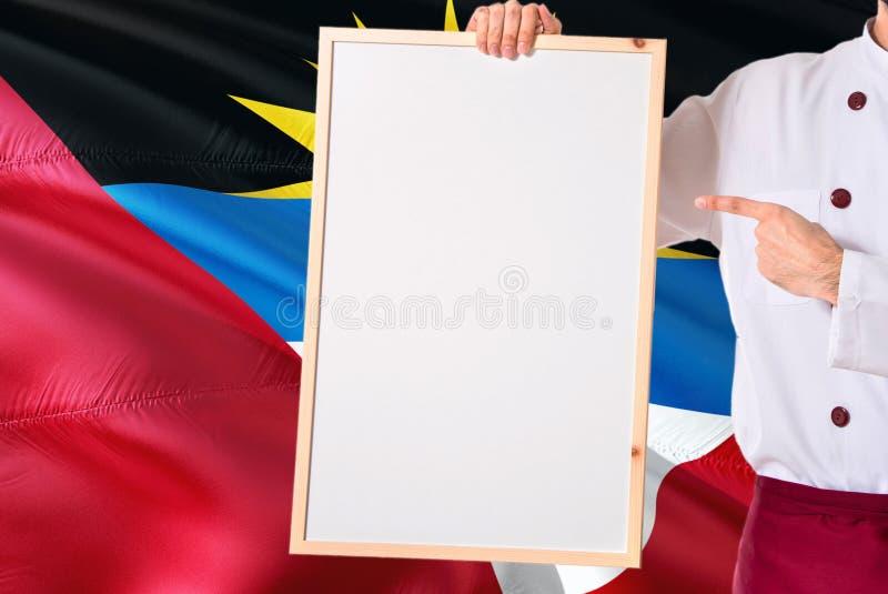 Chef-kok die leeg whiteboardmenu op Antigua en de vlagachtergrond van Barbuda houden Kok die eenvormige richtende ruimte voor tek royalty-vrije stock foto