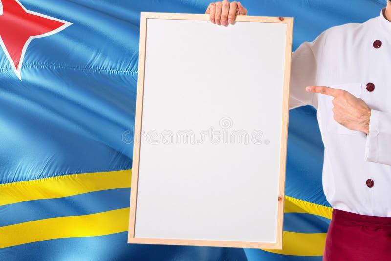 Chef-kok die leeg whiteboardmenu op de vlagachtergrond van Aruba houden Kok die eenvormige richtende ruimte voor tekst dragen royalty-vrije stock fotografie