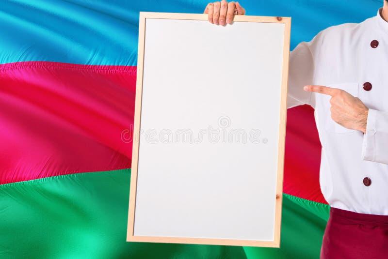 Chef-kok die leeg whiteboardmenu op de vlagachtergrond van Azerbeidzjan houden Kok die eenvormige richtende ruimte voor tekst dra royalty-vrije stock fotografie