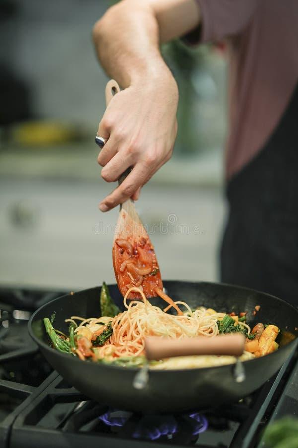 Chef-kok die omhoog een schotel van veganistdeegwaren koken stock foto