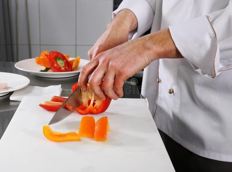 Chef-kok die peper voorbereidt royalty-vrije stock afbeelding