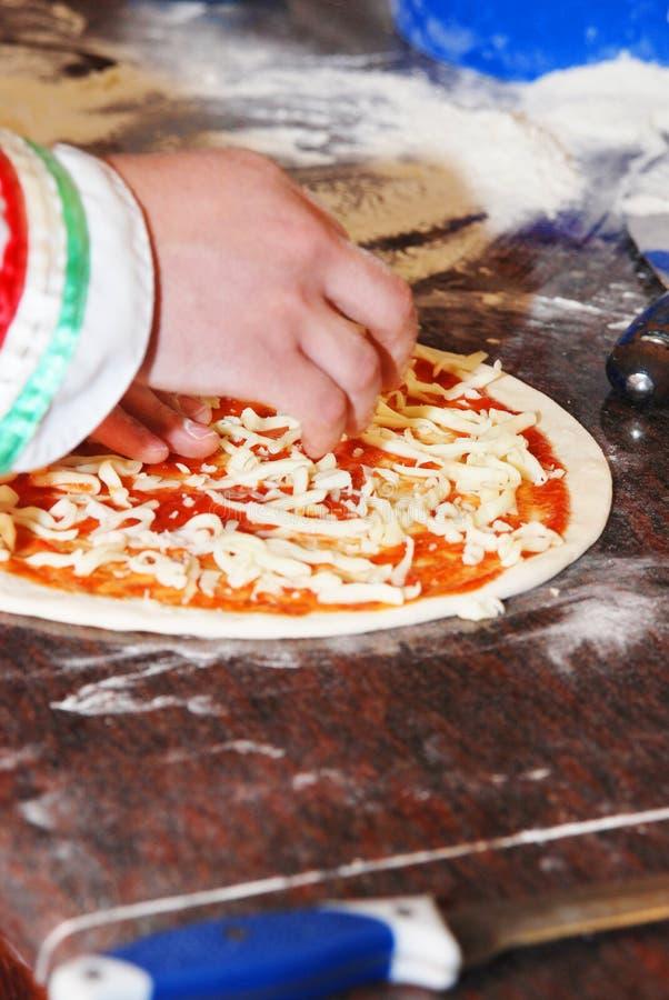 Chef-kok die pizza voorbereidt stock fotografie