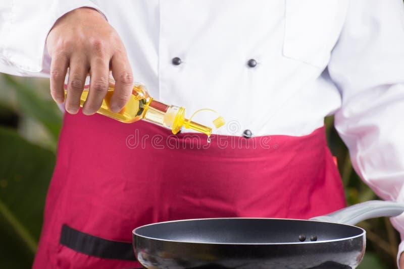 Chef-kok die plantaardige olie gieten aan de pan stock afbeeldingen