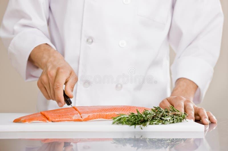 Chef-kok die ruwe zalm snijdt om voor maaltijd voorbereidingen te treffen royalty-vrije stock foto's