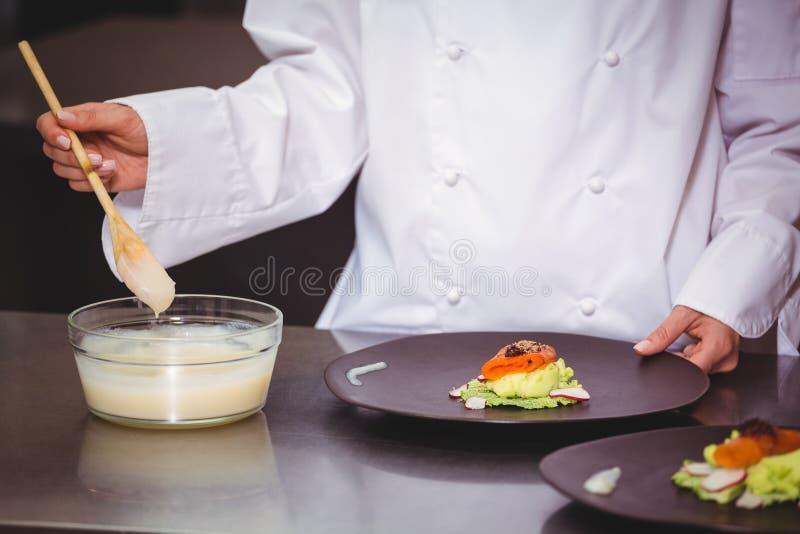 Chef-kok die saus op een schotel zetten stock afbeelding