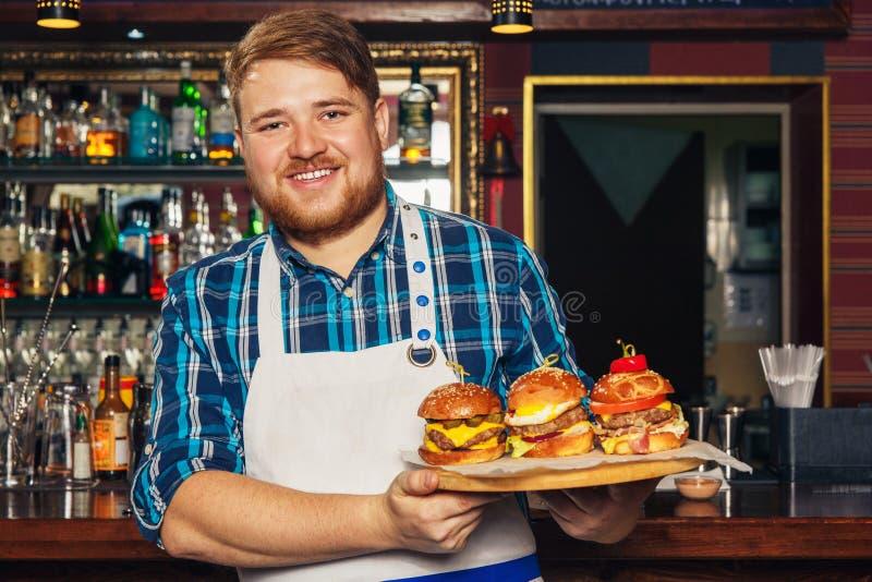 Chef-kok die in schort een dienblad met verschillende heerlijke burgers voorstellen royalty-vrije stock foto's