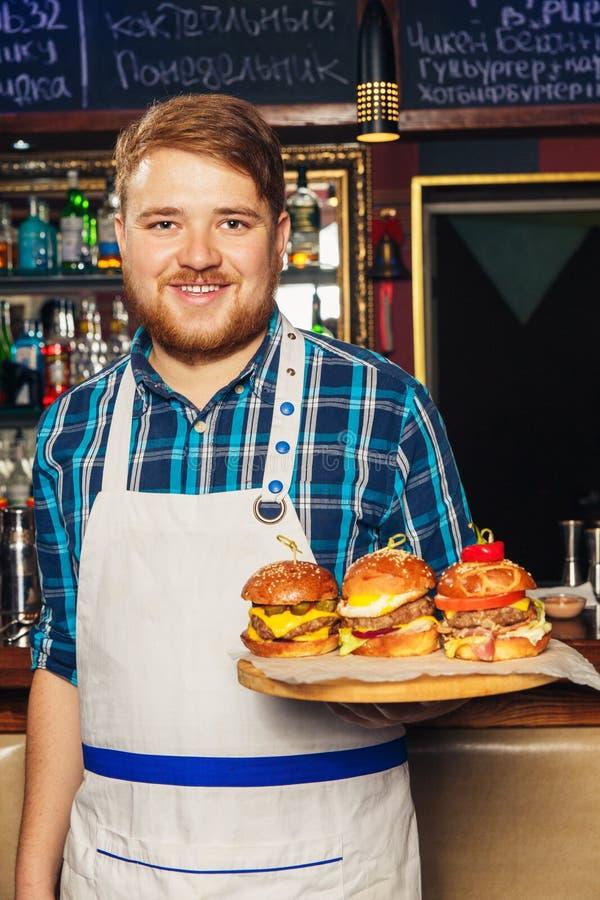 Chef-kok die in schort een dienblad met verschillende heerlijke burgers voorstellen royalty-vrije stock foto