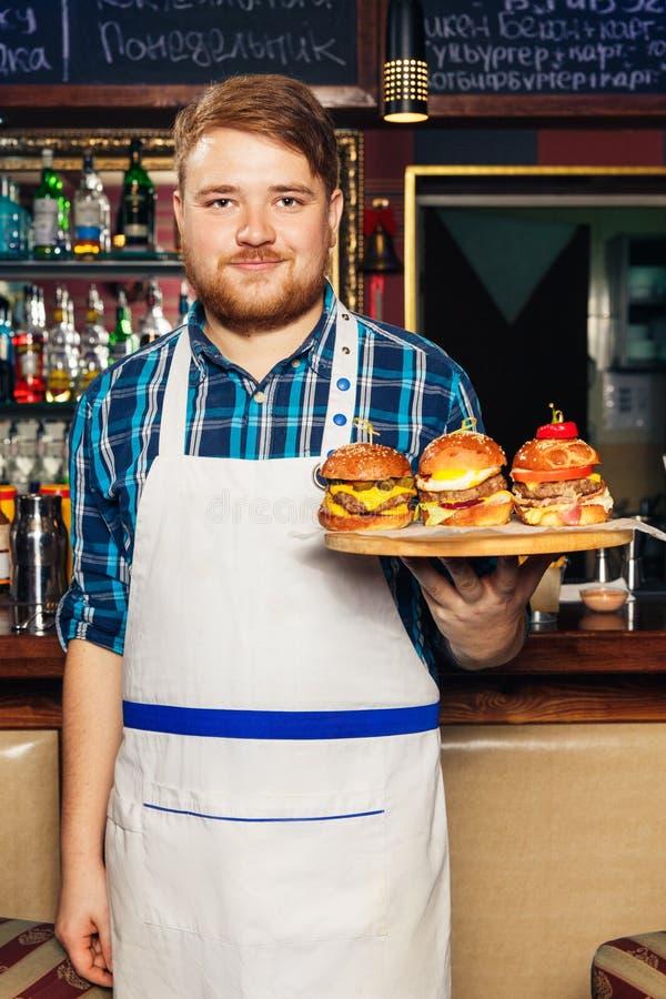 Chef-kok die in schort een dienblad met verschillende heerlijke burgers voorstellen stock foto's
