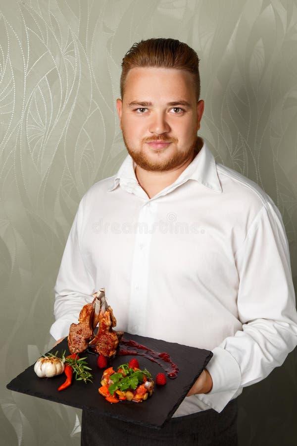 Chef-kok die in schort een dienblad met verschillende heerlijke burgers voorstellen royalty-vrije stock afbeelding