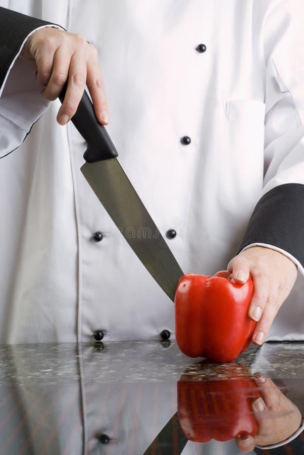 Chef-kok die Spaanse peper snijdt stock foto