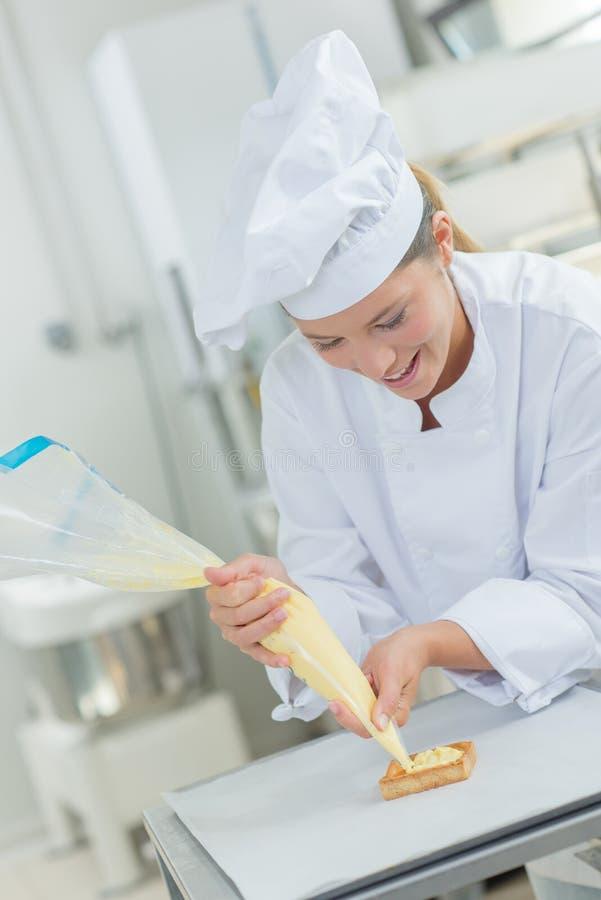 Chef-kok die suikerglazuur op cake zetten stock foto