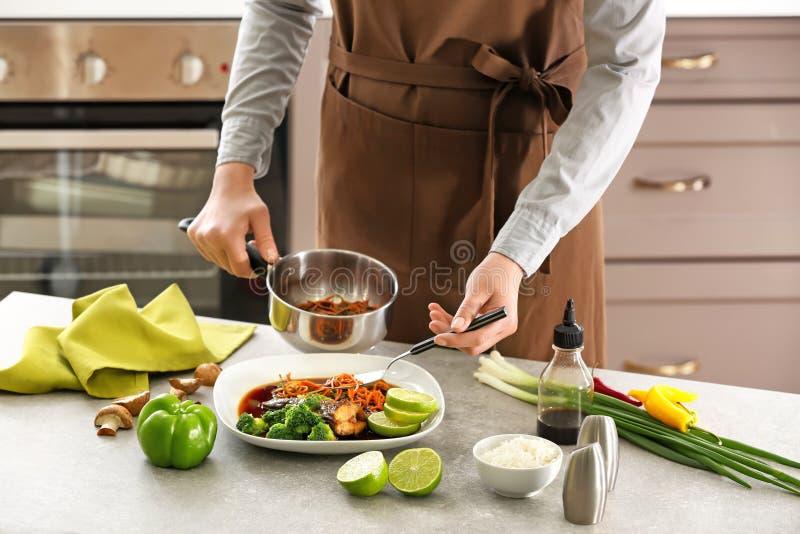 Chef-kok die wortel in saus op plaat met vissen zetten stock afbeeldingen