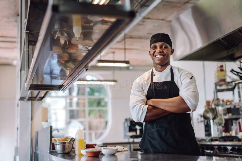 Chef-kok die zich bij restaurantkeuken bevinden royalty-vrije stock foto's