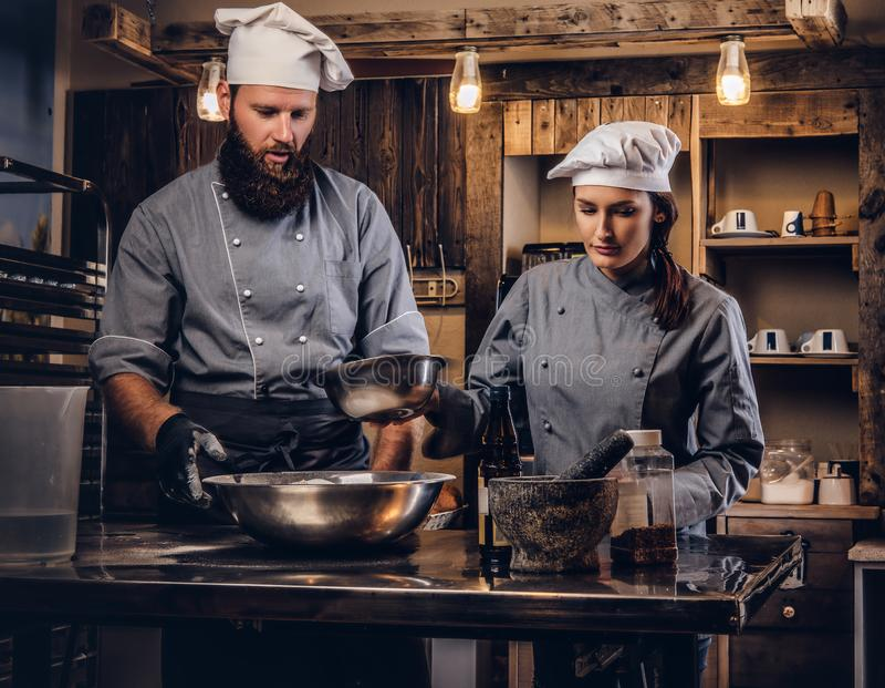 Chef-kok die zijn medewerker onderwijzen om het brood in de bakkerij te bakken stock afbeelding