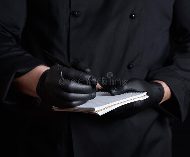 Chef-kok die in zwarte eenvormige en latexhandschoenen een leeg notitieboekje en een zwart houten potlood houden stock afbeeldingen