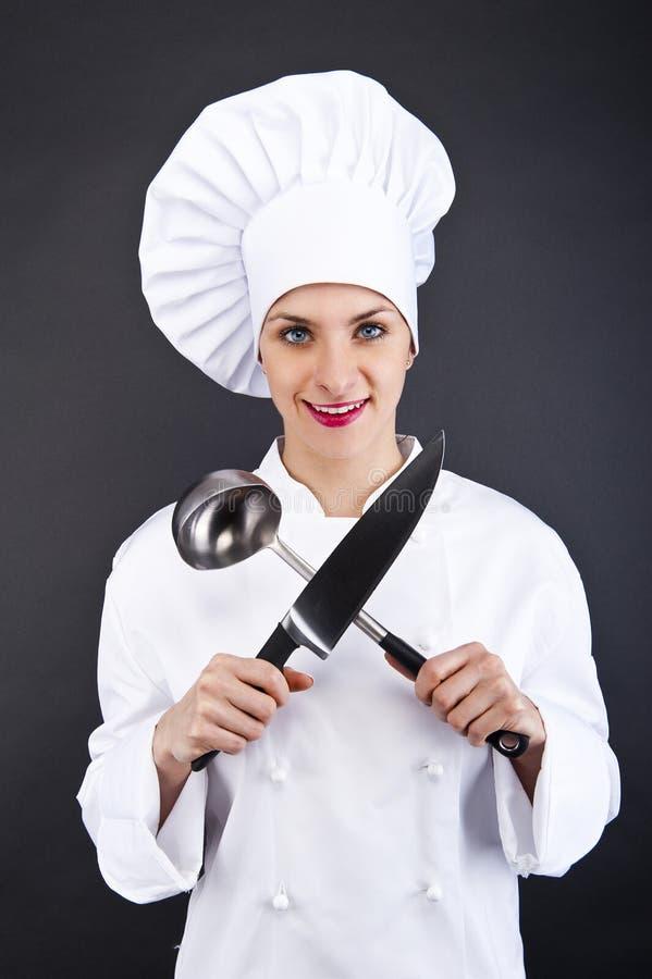 Chef-kok in eenvormige holding een een keukenmes en lepel stock fotografie
