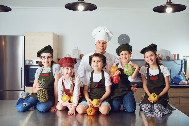 Chef-kok en jonge geitjes met groenten in modieuze keuken royalty-vrije stock afbeelding