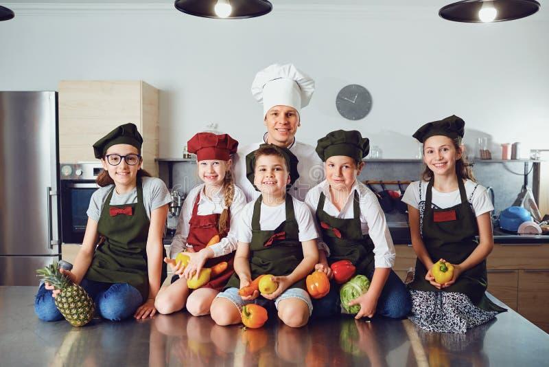 Chef-kok en jonge geitjes met groenten in modieuze keuken stock foto