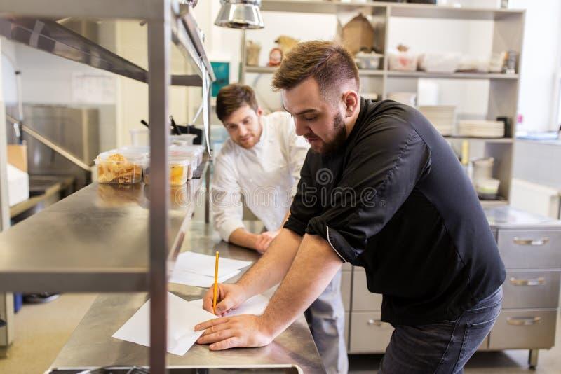 Chef-kok en kok met kruidenierswinkellijst bij keuken stock afbeeldingen