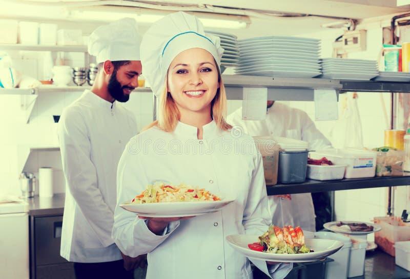 Chef-kok en zijn medewerkers die maaltijd voorbereiden stock afbeelding