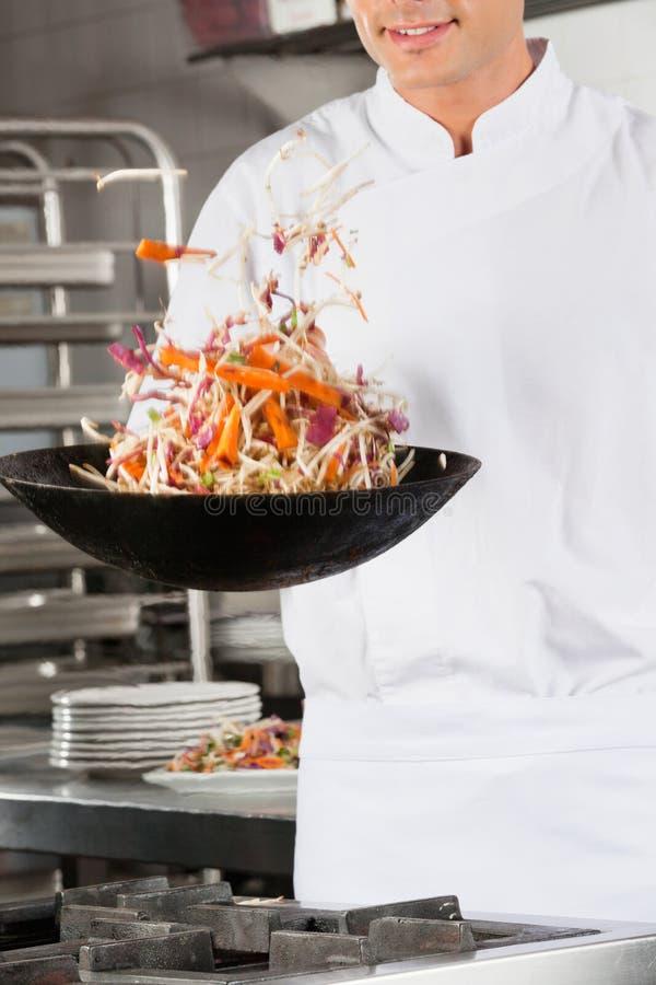 Chef-kok Flipping Vegetables in Wok stock foto's