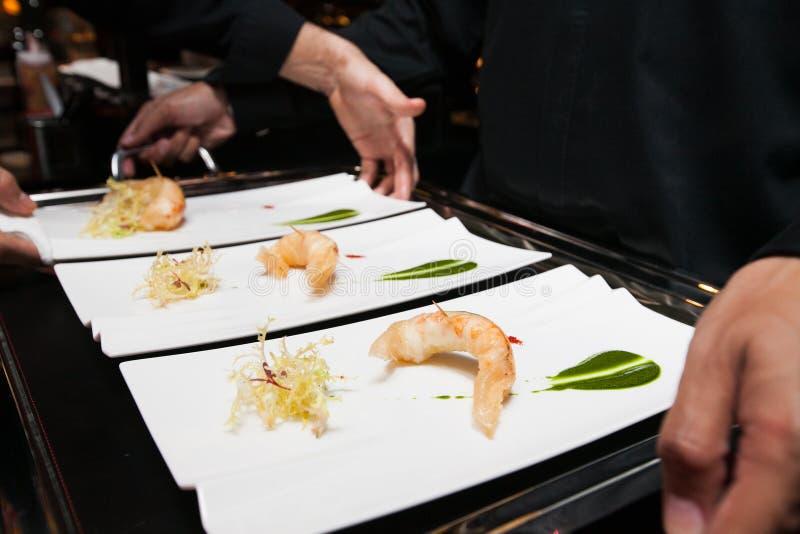Chef-kok gezet voedsel op dienblad vóór gediend door kelner stock afbeelding