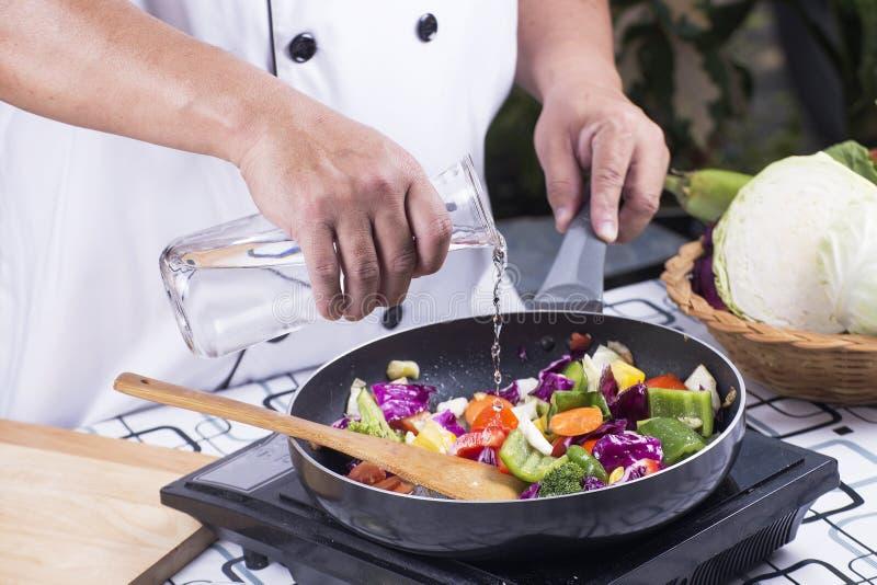 Chef-kok gietende soep aan de pan stock foto