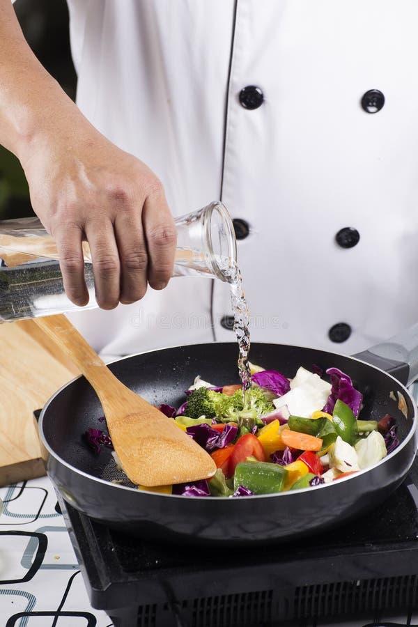 Chef-kok gietende soep aan de pan stock foto's