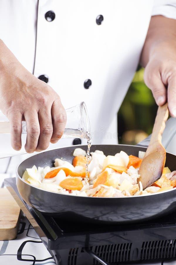 Chef-kok gietende soep aan de pan voor het koken van Japanse varkensvleeskerrie royalty-vrije stock foto
