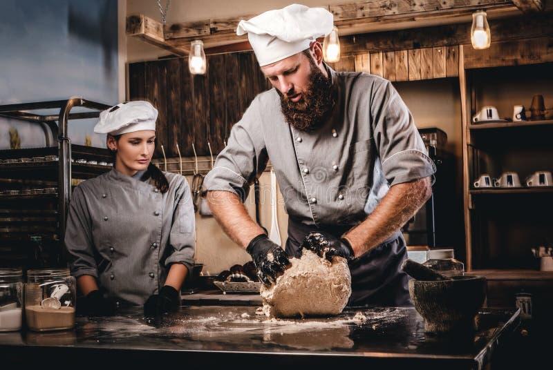 Chef-kok het kneden deeg in de keuken Chef-kok die zijn medewerker onderwijzen om het brood in de bakkerij te bakken royalty-vrije stock fotografie