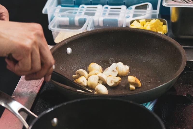 Chef-kok het koken beweegt gebraden gerechtpaddestoel in pan wordt gesneden die royalty-vrije stock foto