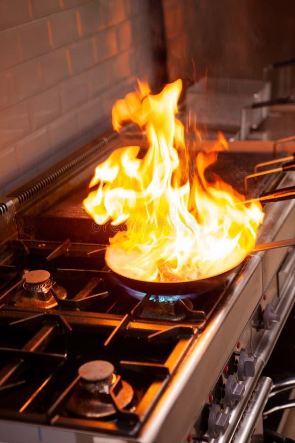 Chef-kok het koken met hoge brand in keuken royalty-vrije stock afbeelding