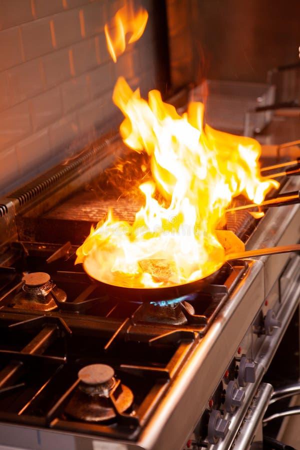 Chef-kok het koken met hoge brand in keuken stock afbeeldingen