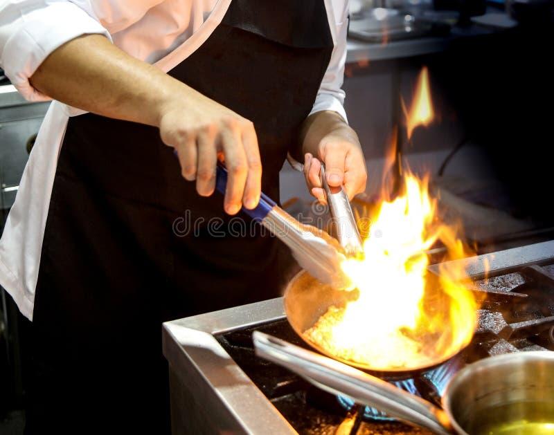 Chef-kok het koken met vlam in een pan op een keukenfornuis royalty-vrije stock fotografie