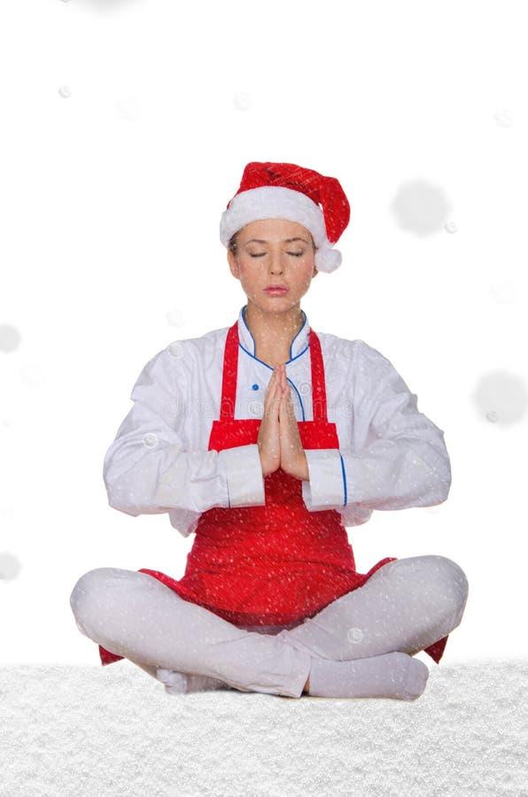 Chef-kok in hoed die van Kerstman yoga met sneeuw doen royalty-vrije stock afbeelding