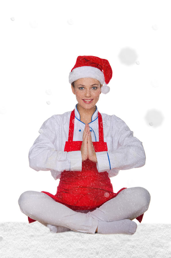 Chef-kok in hoed die van Santa Claus yoga met sneeuw doen stock foto's